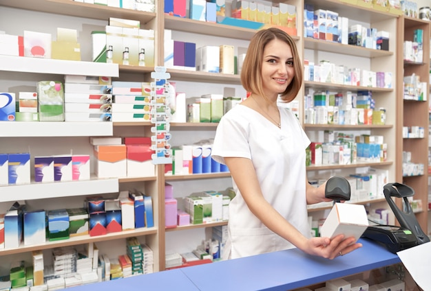 Счастливый фармацевт, сканирование штрих-кода медикамента. Premium Фотографии