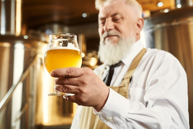 Пожилой пивовар с бокалом светлого пива Premium Фотографии