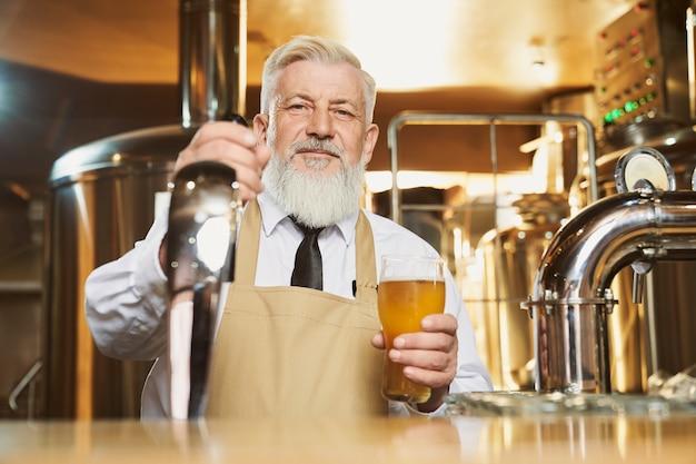 Пожилой бармен стоит у барной стойки с пивным бокалом Premium Фотографии