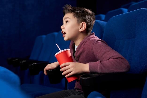 Возбужденный подросток с просмотром боевика в кино Premium Фотографии