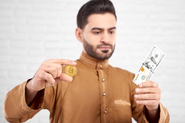 彼の手で黄金のビットコインを保持しながら百ドルを見てハンサムな若いイスラム教徒の男性 Premium写真