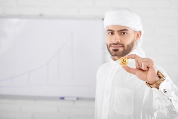 Богатый красивый мусульманин в традиционной исламской одежде держит золотой биткойн перед белой доской Premium Фотографии