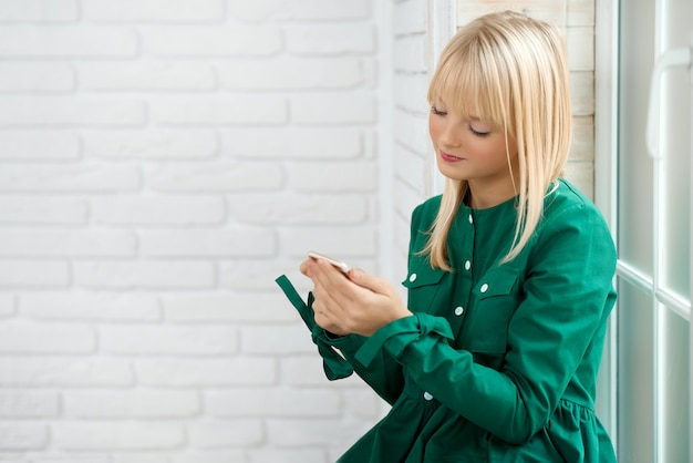 Молодая женщина с помощью смартфона Premium Фотографии