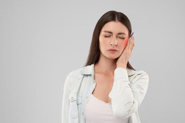 Женщина показывает боль в ухе Premium Фотографии