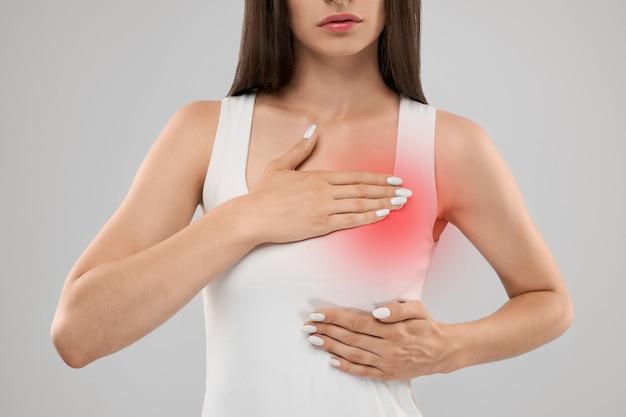 Женщина показывает боль в груди Premium Фотографии