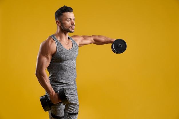 Атлетик молодой человек делает упражнения на бицепс Premium Фотографии