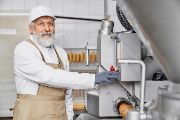 近代的な設備に近いポーズの肉工場の労働者。 Premium写真