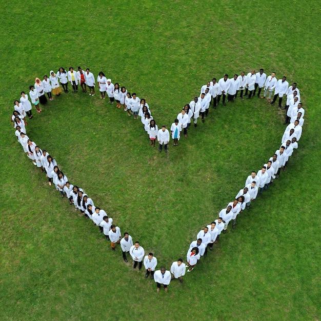 若い医学生が地面に立って、大きなチャリティーハートを作ります。 Premium写真