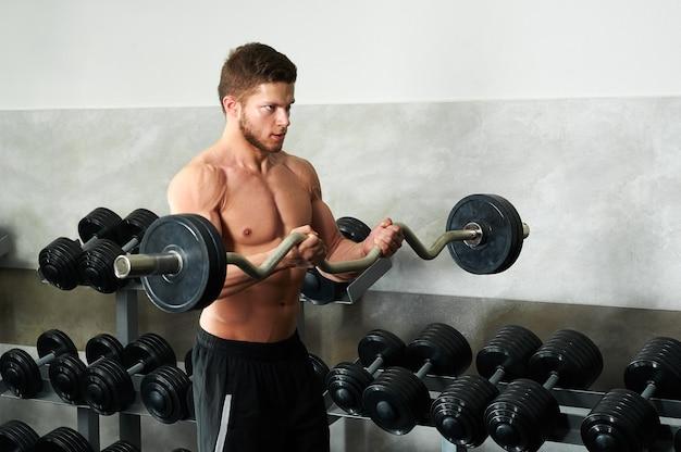 ジムで上腕二頭筋を行う若い筋肉質の選手 Premium写真