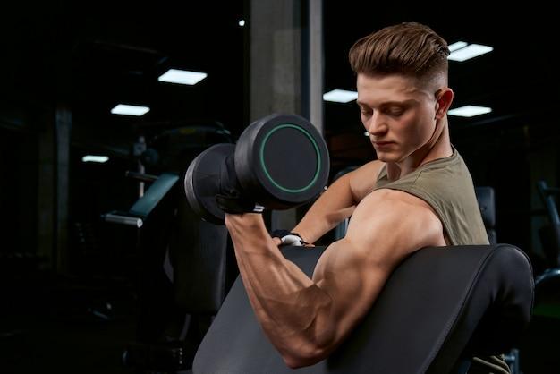 Спортсмен тренирует бицепс с гантелями. Бесплатные Фотографии