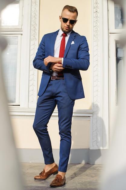 青いスーツを着てポーズを取るハンサムな男性モデル。 Premium写真