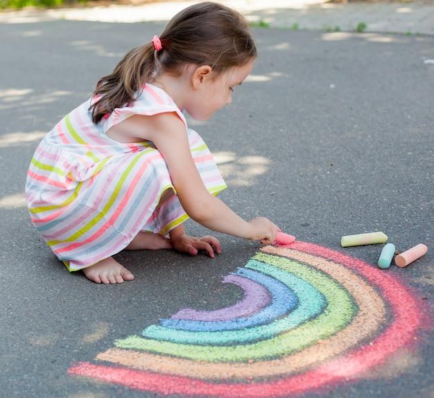 Ребенок девочка рисует радугу с цветным мелом на асфальте. Premium Фотографии