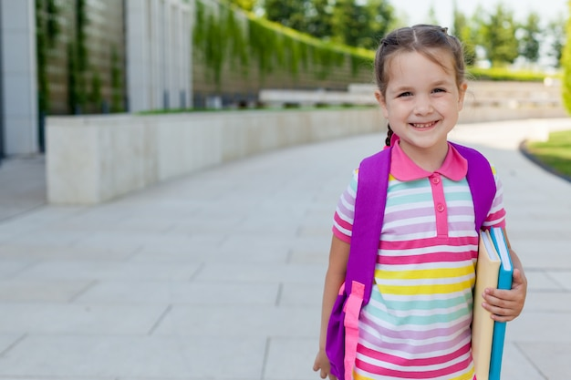 幸せな子供女の子小学生が授業に駆けつけます。 Premium写真