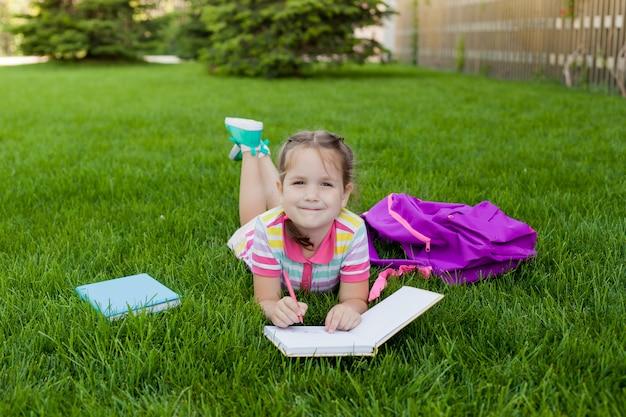 子供女の子女子高生小学生は草の上に横たわるし、ノートに描画します。学校に戻る概念。野外活動 Premium写真