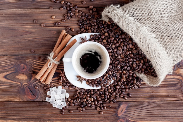 コーヒーカップとテーブルの上のコーヒー豆 Premium写真