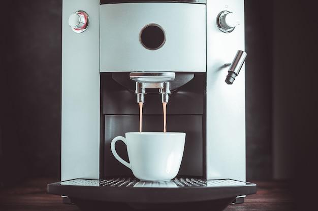 マシンから注ぐコーヒーエスプレッソのクローズアップ Premium写真