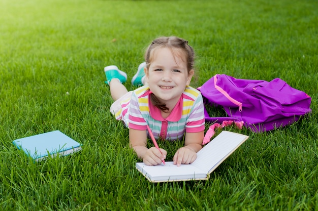 Ребенок девочка школьница ученик начальной школы лежа на траве и рисует в записной книжке. Premium Фотографии