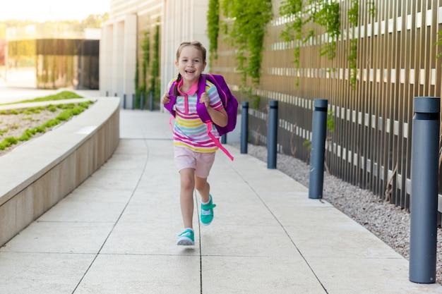学校に戻る概念。学校の初日。幸せな子供の女の子はクラスに実行されます。 Premium写真