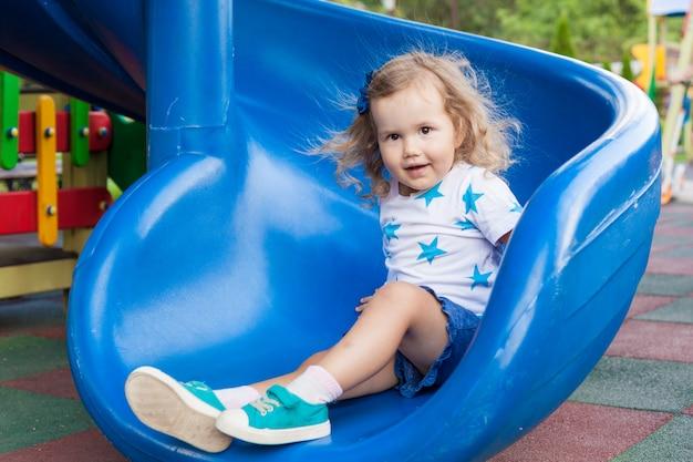 日当たりの良い夏の日に屋外の遊び場で楽しんでいるかわいい女の子。プラスチック製のスライドの子。子供のための楽しい活動。 Premium写真