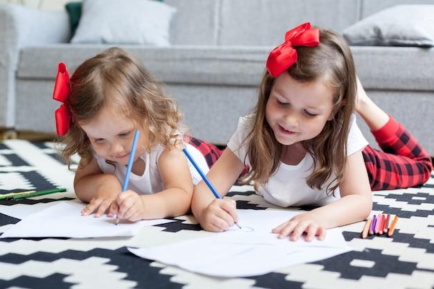二人の少女姉妹が家の床に横になり、紙に色鉛筆で描きます。 Premium写真