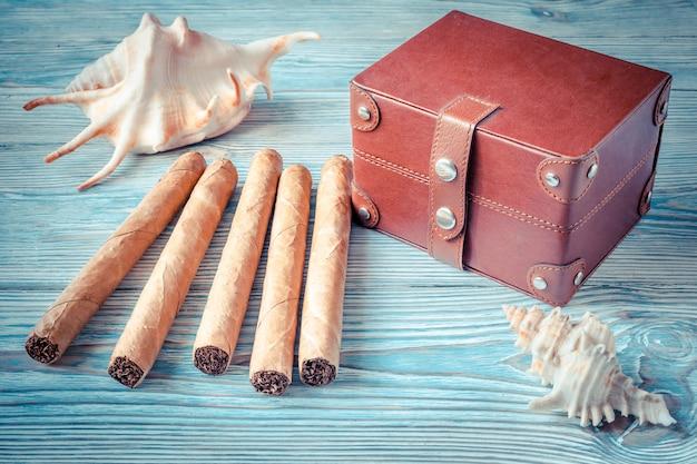 キューバ産の葉巻、貝殻、青い木製テーブルの上の小さな胸。休暇の思い出 Premium写真