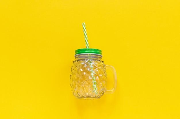 Пустая стеклянная банка в форме ананаса с зеленой крышкой и соломкой для фруктовых или овощных напитков Premium Фотографии