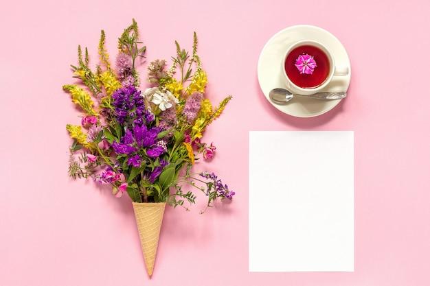 ブーケ色のアイスクリームワッフルコーン、紅茶と空白の紙カードの花 Premium写真