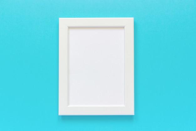 青の背景に空のカードを持つホワイトフレーム Premium写真