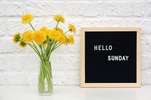 こんにちは黒い文字板とテーブルの上の黄色のタンポポの花の花束の日曜日の言葉 Premium写真