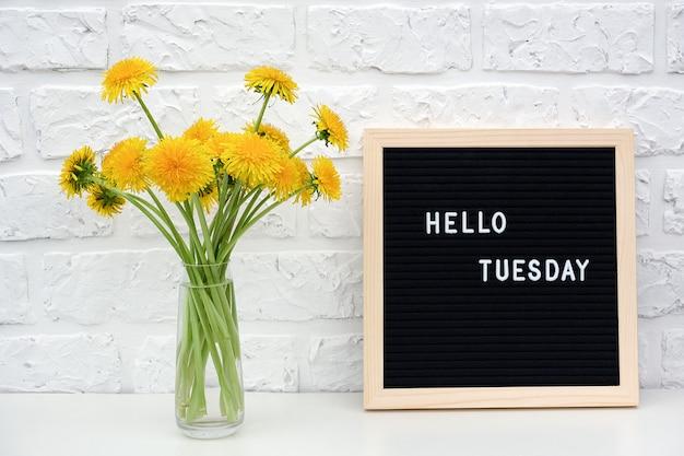 こんにちは、ブラックレターボード上の火曜日の言葉と黄色のタンポポの花の花束 Premium写真