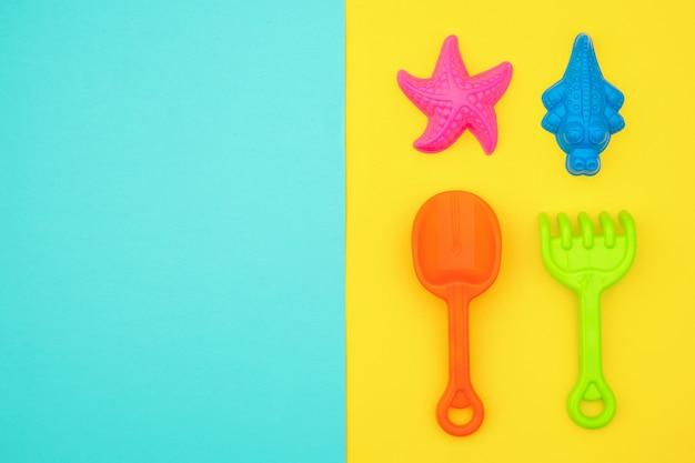 砂場またはコピースペースと青黄色の背景に砂浜で夏のゲームの色とりどりのセット子供のおもちゃ Premium写真