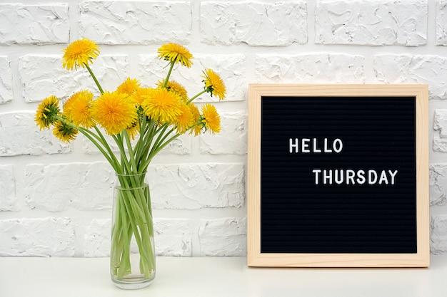 こんにちは、黒い文字板に木曜日の言葉と白いレンガの壁にテーブルの上の黄色のタンポポの花の花束。 Premium写真