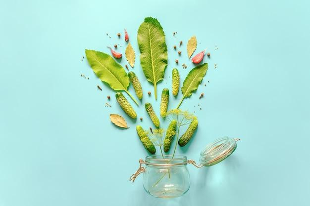 きゅうりのピクルス。青の背景にピクルスのマリネとガラスの瓶の材料。コンセプト料理レシピ Premium写真