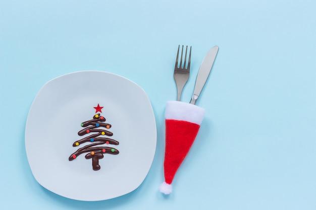 プレートとカトラリーに甘いチョコレートクリスマスツリー Premium写真