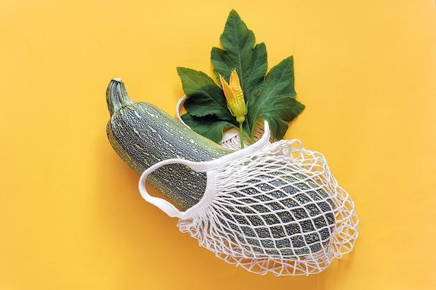 再利用可能なショッピング環境にやさしいメッシュバッグに緑の葉と花と新鮮なズッキーニ Premium写真