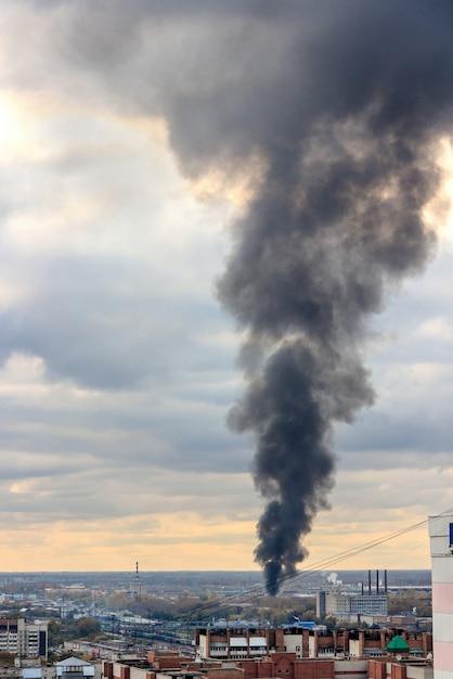 火事による煙の黒い柱が空に上がる。 Premium写真