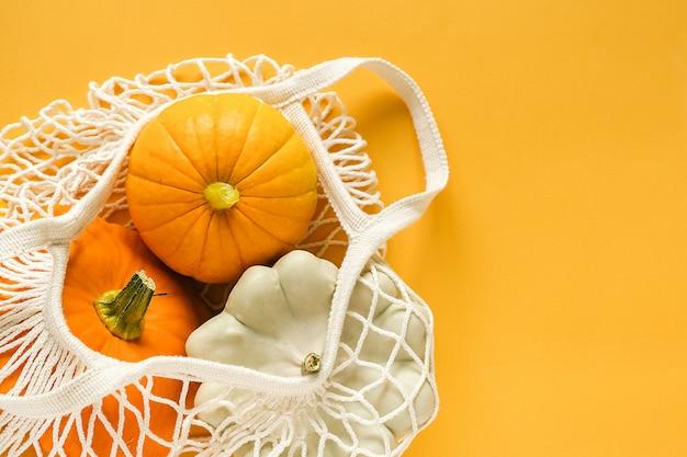新鮮な収穫野菜ひょうたんカボチャ、黄色の背景にショッピングエコメッシュバッグでパティパンスカッシュ。 Premium写真