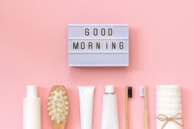 ライトボックステキストおはようと化粧品のセットとシャワーまたはピンクの背景のお風呂のツール Premium写真