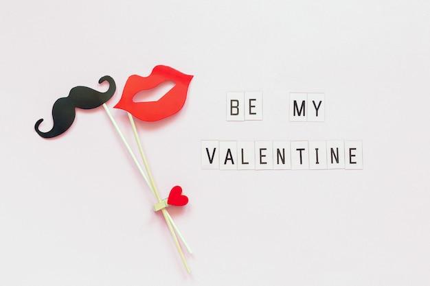 Текст будь моим валентином и парой бумажных усов, губы подпирают скрепленную прищепкой сердце на палочке на розовом Premium Фотографии
