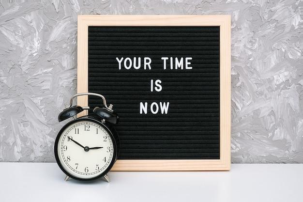 あなたの時間は今、文字板上の動機付けの引用と石の壁にテーブルの上の黒い目覚まし時計です。 Premium写真