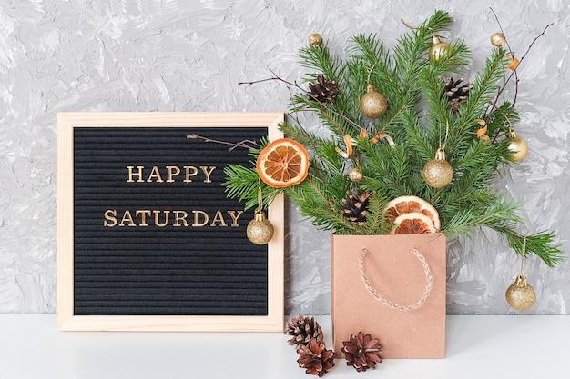 黒文字板とテーブルの上のクラフトパッケージでクリスマスの装飾が施されたモミの枝のお祝いブーケに幸せな土曜日のテキスト。 Premium写真