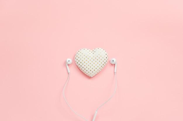 Декоративные текстильные объемные сердечки и белые наушники на розовом фоне Premium Фотографии