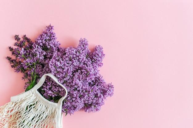 こんにちは春。白い再利用可能なショッピングエコメッシュバッグコンセプトにライラックの明るい花束プラスチック、無駄なし。 Premium写真