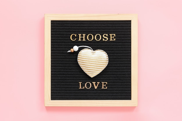 Выбрать любовь. мотивационные цитаты золотыми буквами и текстильного сердца на черной доске письма. вид сверху Premium Фотографии