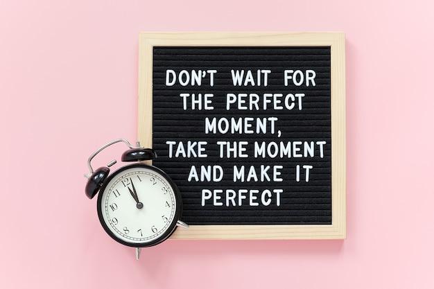 Не ждите идеального момента, используйте его и сделайте его идеальным. мотивационная цитата на доске объявлений, черный будильник Premium Фотографии