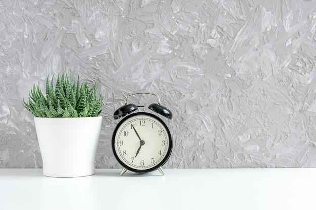 黒の目覚まし時計とテーブル、灰色のコンクリートの壁に白い鍋に緑の多肉植物。 Premium写真