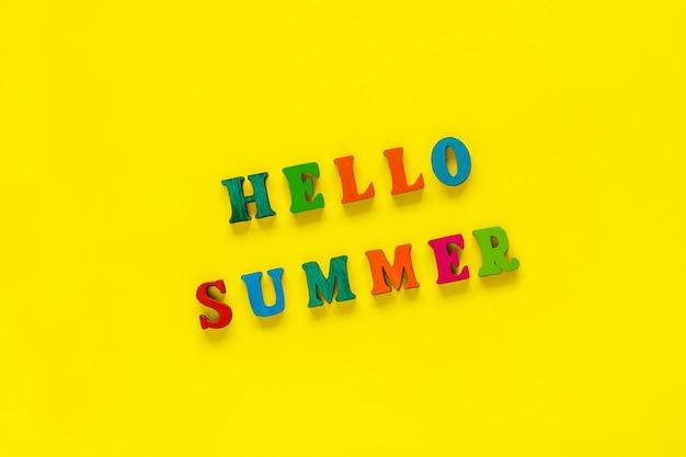 黄色の背景にカラフルな文字から碑文こんにちは夏、 Premium写真