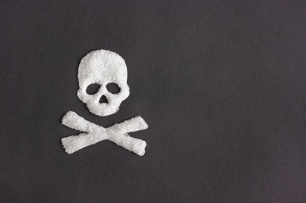 黒の背景、概念上の砂糖から頭蓋骨形状 Premium写真