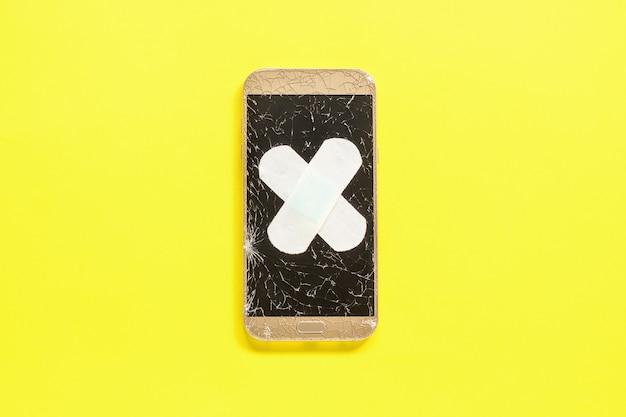 黄色の石膏で固定ひびの入った画面を持つモバイルスマートフォン Premium写真