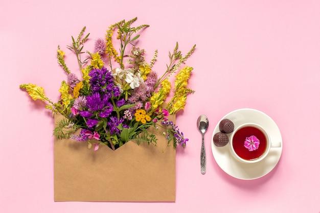 クラフト封筒とハーブティーのカップの野の花 Premium写真